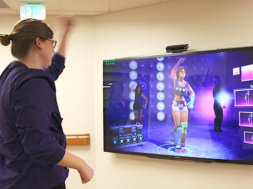 A nurse demonstrates the Xbox Kinect just inside the unit