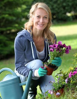 middle-aged woman happily gardening